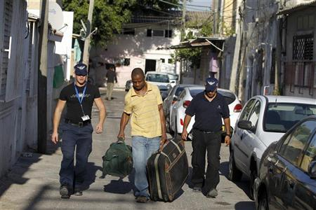Israeli immigration officers escort an African migrant in south Tel Aviv