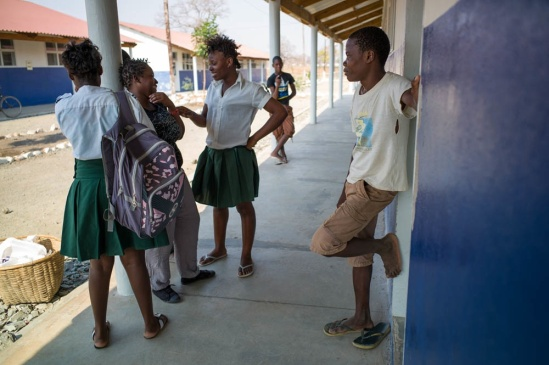 """Students hang around after school at Armando Guebuza School in Cateme. The school is a so-called """"white elephant"""": theoretically it brings education and infrastructure to the resettlement, but in reality not many families can afford the high school and examination turning the school into a de facto boarding school for students from other communities. Only approximately 10 percent of students come from Cateme resettlement."""